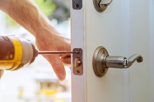 serrure d'une porte en réparation avec une dévisseuse